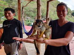 Becky gets to play with a squirrel monkey while our guide, Junior, looks on; Monkey House