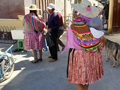 Traditionally dressed women shopping with babies in tow; Uyuni