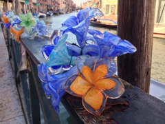 Glass flowers decorate the waterfront; Murano