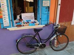 A bike parked in front of an intersection of color; Burano
