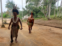 Two teenagers laugh as they greet tourists; Rio Negro village visit