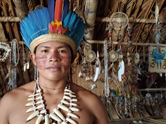 Posing in his traditional outfit, an indigenous boy stifles a smile; Rio Negro