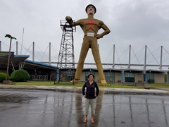 Becky standing between the legs of the Golden Driller Statue, a 75 foot statue weighing 43,500 pounds in Tulsa, Oklahoma