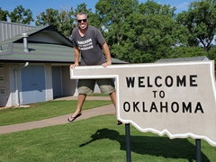 "Robby on a ""Welcome to Oklahoma"" sign"