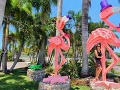 Becky next to giant flamingos at the Marietta Museum of Art & Whimsy; Sarasota
