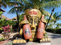 Grinning tiki head holding two beer bottles at Yucatan Restaurant; Fort Myers