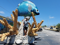 Becky poses next to a massive fish and coral; Marathon