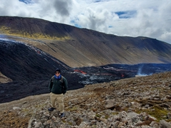 Hot lava spilling behind Robby from Geldingadalir volcano