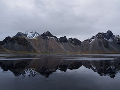 A lovely reflection of Vestrahorn Mountain on the black sand beach