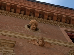 Terra cotta capricci busts on the facade of the Palazzo Bolognini Amorini Salina;  Piazza Santo Stefano