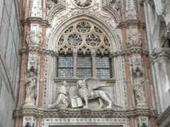 Marble statue of the Doge kneeling before the winged Lion of St Mark (with its paw on the gospel); facade of the Doge's Palace