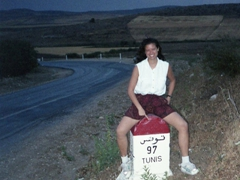 "On the drive from Dougga to Tunis, Becky poses next to a ""97"" Kilometer marker. The guys all took their pics next to the ""96"" marker (indicating the year we'd graduate)"