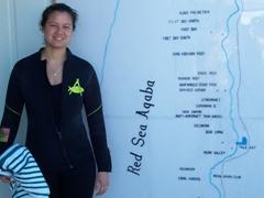 Becky beside an Aqaba dive site map