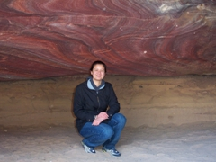 Becky poses beneath a section of the rose red rock formations that Petra is famous for
