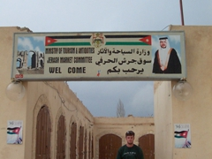 """Robby beneath a """"Welcome to Jerash"""" signpost"""