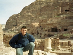 Robby striking a pose with dozens of rock cut tombs of various shapes and sizes in the background