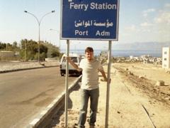 Robby under a Durra (Saudi Arabia) border crossing sign; Aqaba