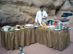 Our Bedouin host sets up dinner, a scrumptious meal of barbequed chicken and lamb, fresh tomato and cucumber salad, delicious humus and pita bread