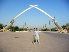 The Hands of Victory triumphal arch, an entrance way to a large parade ground in Baghdad. The arch is created from 2 crossed swords weighing 24 tons (cast from the guns of dead Iraqi soldiers), and at the base of each arm are a collection of captured Iranian helmets