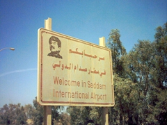 This sign sure doesn't exist anymore. Every statue or signpost referencing Saddam has since been removed