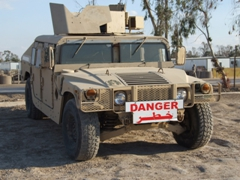 "An HMMWV with a clearly marked ""danger"" sign in English and Arabic (so that civilian traffic does not get too close during convoys); Camp Victory"