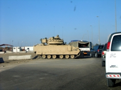 An armored personnel carrier at a military checkpoint helps to control entering traffic