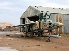 A graffitied MiG-23 sits forlornly by itself; Balad