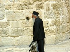 A clergy member strolls past on on his way to the Church of the Holy Sepulchre