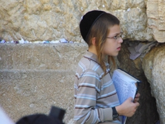 A young Jewish boy takes a break from his recitations in front of the Western Wall (full of white prayer slips); Jerusalem