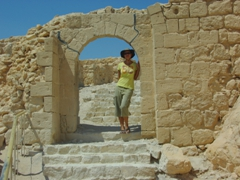 Becky standing beneath the Byzantine Western Gate of the Masada Fortress