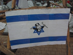"A ""monopoly"" figure pops out of this star of David on this Israeli flag in a staged protest in Tel Aviv"