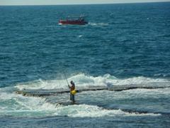 A fisherman stands precariously in the sea; Akko