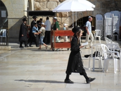 A Jewish boy paces back and forth at the Western Wall praying fervently; Jerusalem