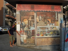 """Robby """"grabs"""" a handful of peanuts from this life-like painting on the side of a building in New Jerusalem"""