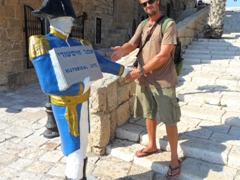 Robby strikes a silly pose with a statue pointing to Old Jaffa's visitor's center