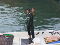 A friendly fisherman waves in greeting; Kuwait harbor