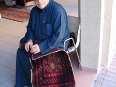 An elderly Kuwaiti man takes a break from working on his carpet