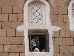 Man peering through one of Dar al-Hajar's windows