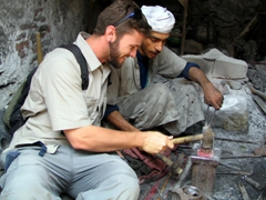 Robby lending his unskilled assistance to a blacksmith in the suq, Sana'a