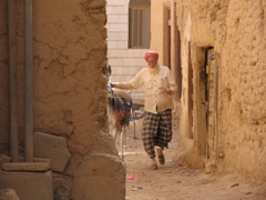 Man leading his donkey through Al-Hajarain's narrow alleyways