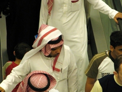 """View of Gulf men wearing traditional outfits. Their white robes are known as """"dishdasha"""", and their red & white checkered headdress is known as """"gutra"""". The gutra is held in place by a black cord referred to as an """"agal"""""""
