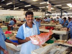 A vendor proudly showing off his red snapper for sale, Dubai Fish Market