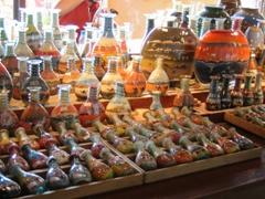 Sand art arranged in various sized glass bottles for sale; Madinat Jumeirah Souk
