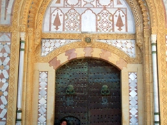 Becky crouches beside a tiny entrance in the larger portal Beiteddine Palace