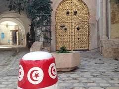 A Tunisian flag painted traffic pylon with a traditional door in the background