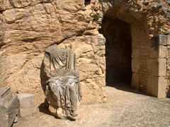A headless seated statue near Dougga theater