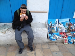 """Robby chowing down on a Sidi Bou Said addictive snack, the sugar coated Italian donut called a """"bambaloni"""""""