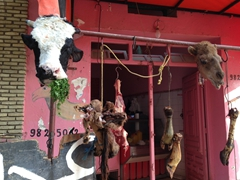 A butcher's shop showcases a cow and camel head to indicate how fresh the meat is