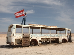 Ala poses with his beloved football team's flag atop a decrepit bus; Chott el Jerid