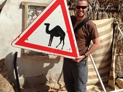 """Robby holds up a """"yield to camel"""" sign; Bir Soltane"""